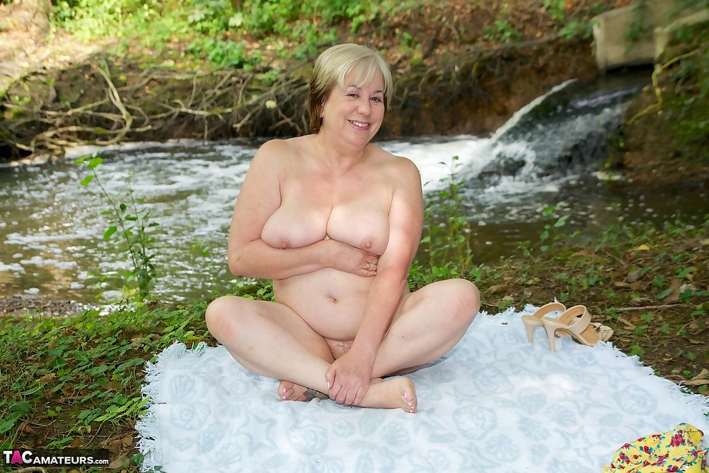 Thick mature woman Speedybee strips naked on a blanket down by the river