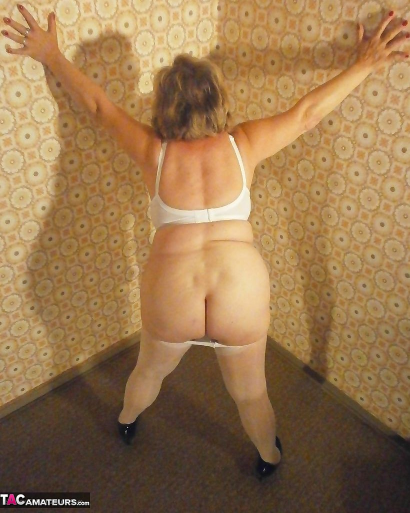 Big ass mature lady Caro posing in white pantyhose and black high heels