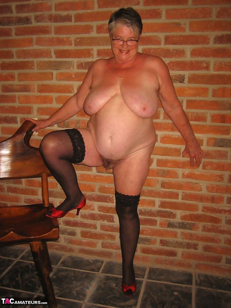 Fat old woman strips to black stockings and heels with her glasses on