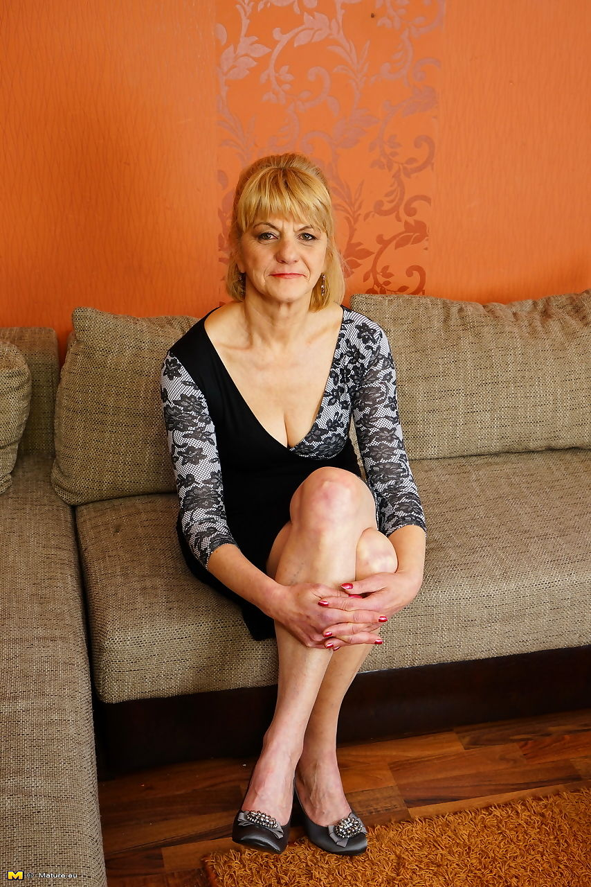 Mature lady hikes up her dress to expose up skirt underwear on her sofa