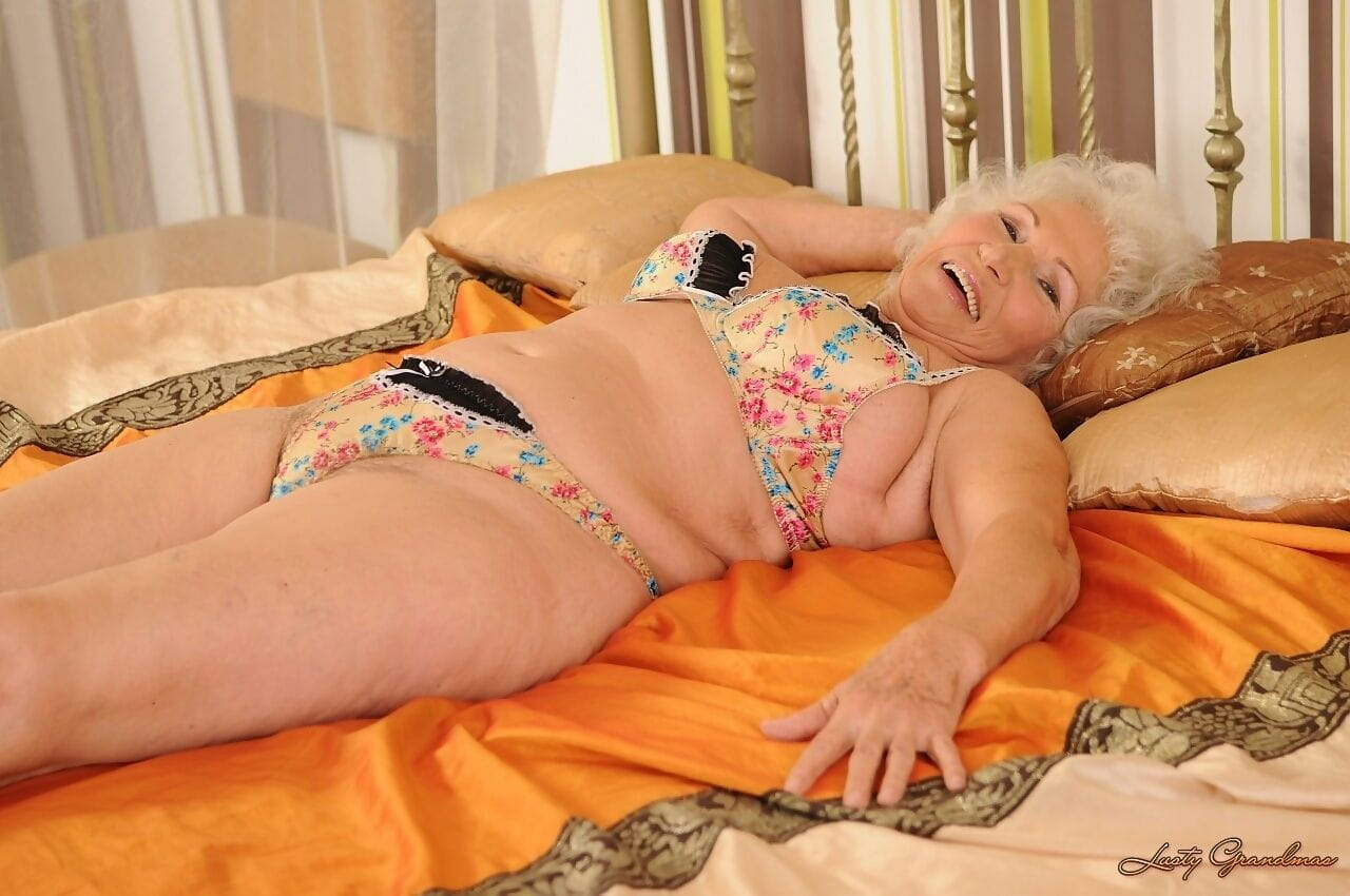 Curly haired granny Norma toying her mature hairy vagina in bed