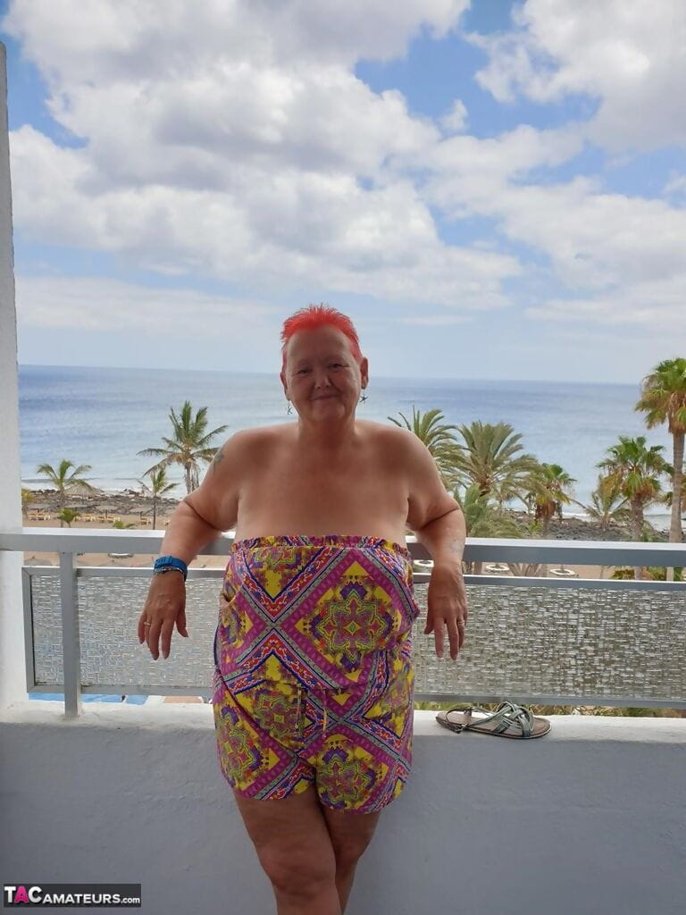 Obese nan with spiky red hair unveils her tits on balcony before posing naked