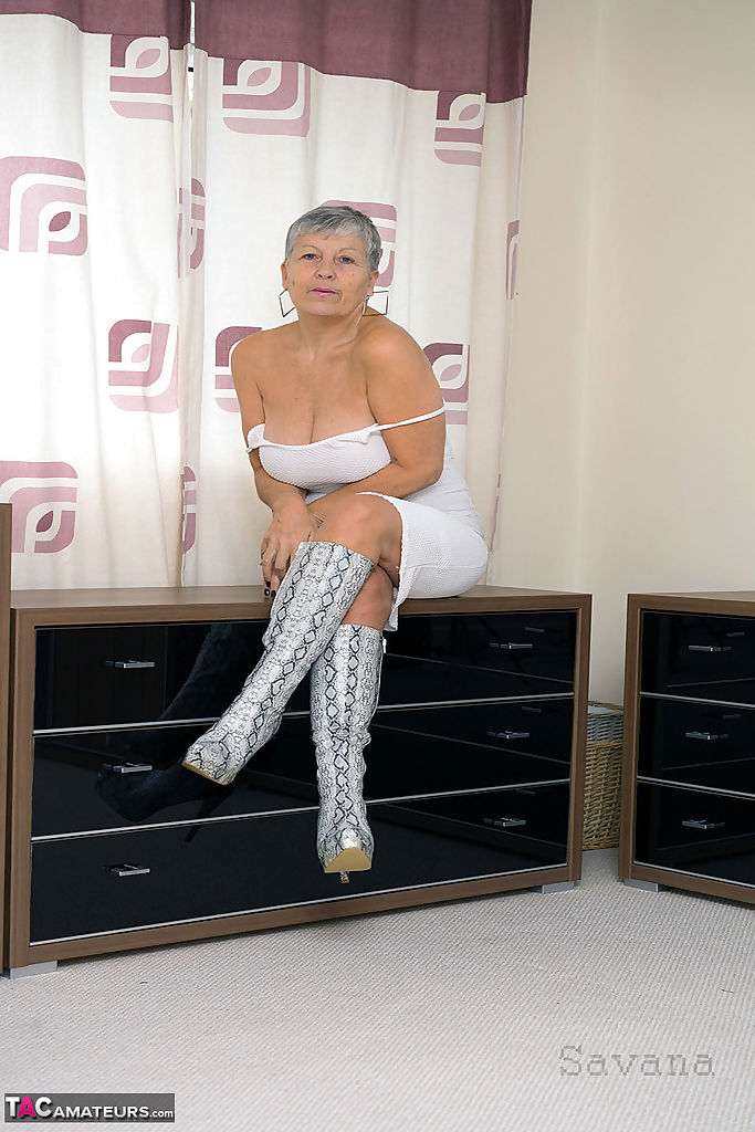 Fun loving hot granny Savana squats to flash naked upskirt in high heel boots