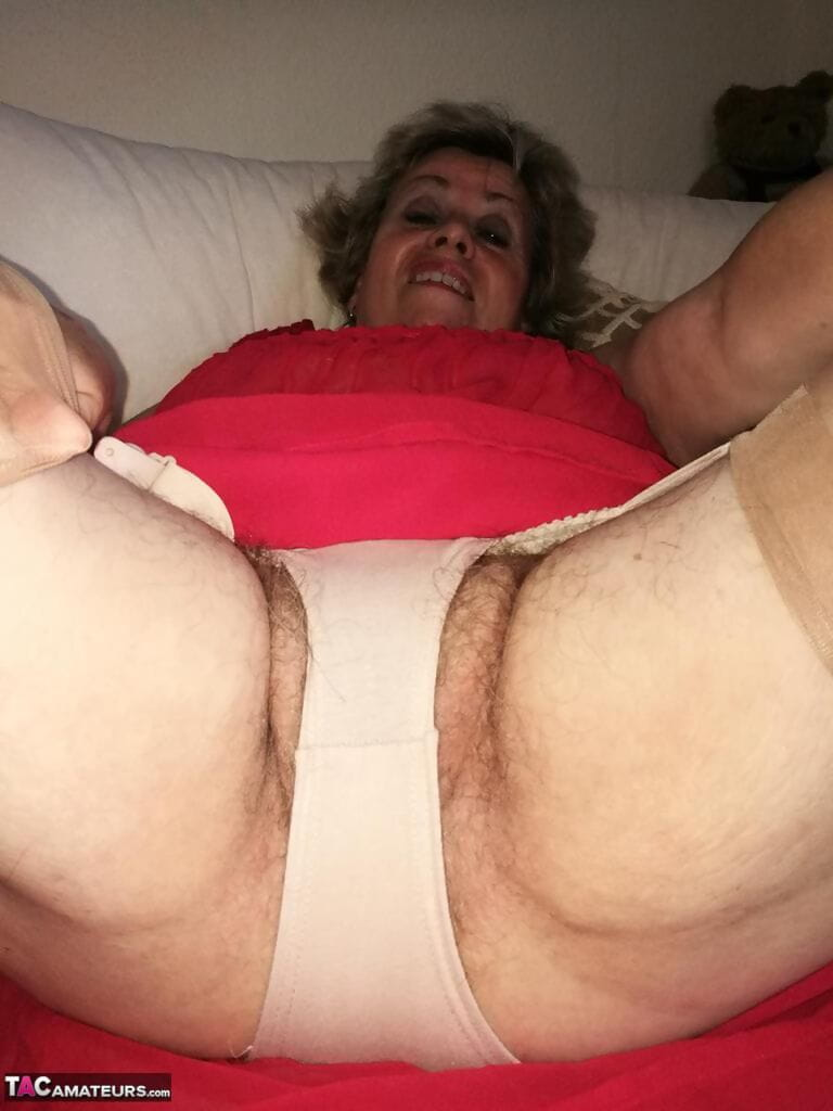 Horny oma Caro hikes up long red dress to spread her hairy vagina